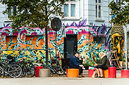 Colourful street art lines the buildings on a street in Vesterbro Copenhagen while a couple enjoy their lunch conversation.