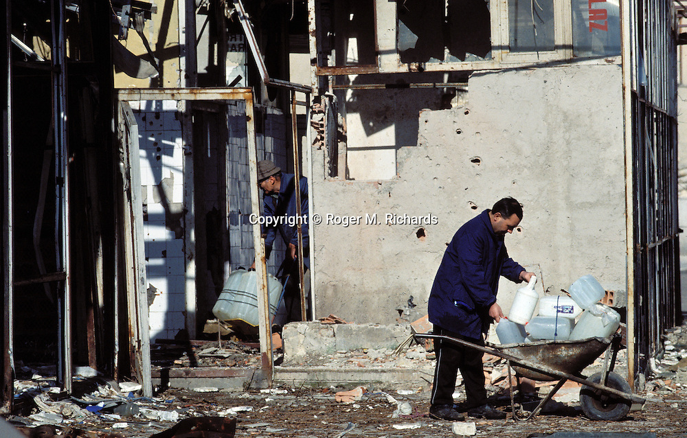 Two men collect water from a pipe in a destroyed building during the Bosnian Serb siege of Sarajevo, Bosnia and Herzegovina, April 1993. Almost 2,000 children, and over 10,000 people in total were killed in Sarajevo during the 3-1/2 year siege. (Photo by Roger Richards)