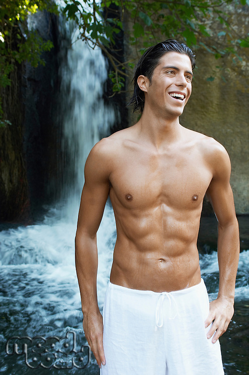 Smiling young man standing by waterfall front view