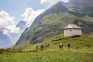 Hikers passing chapel on the Via Alpina, Swiss Alps
