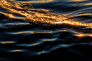 The golden glint cast by the setting sun stretches across a small wave on Puget Sound near the Edmonds, Washingotn, waterfront.