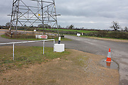 An electricity pylon stands astride a car park at a local Rugby club on land near Wrington, North Somerset England.