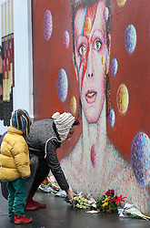 © Licensed to London News Pictures. 11/01/2016. London, UK. A woman lays flowers at a mural of David Bowie in Brixton. The Death of David Bowie, who was born in Brixton, has been announced today.  Photo credit: Peter Macdiarmid/LNP