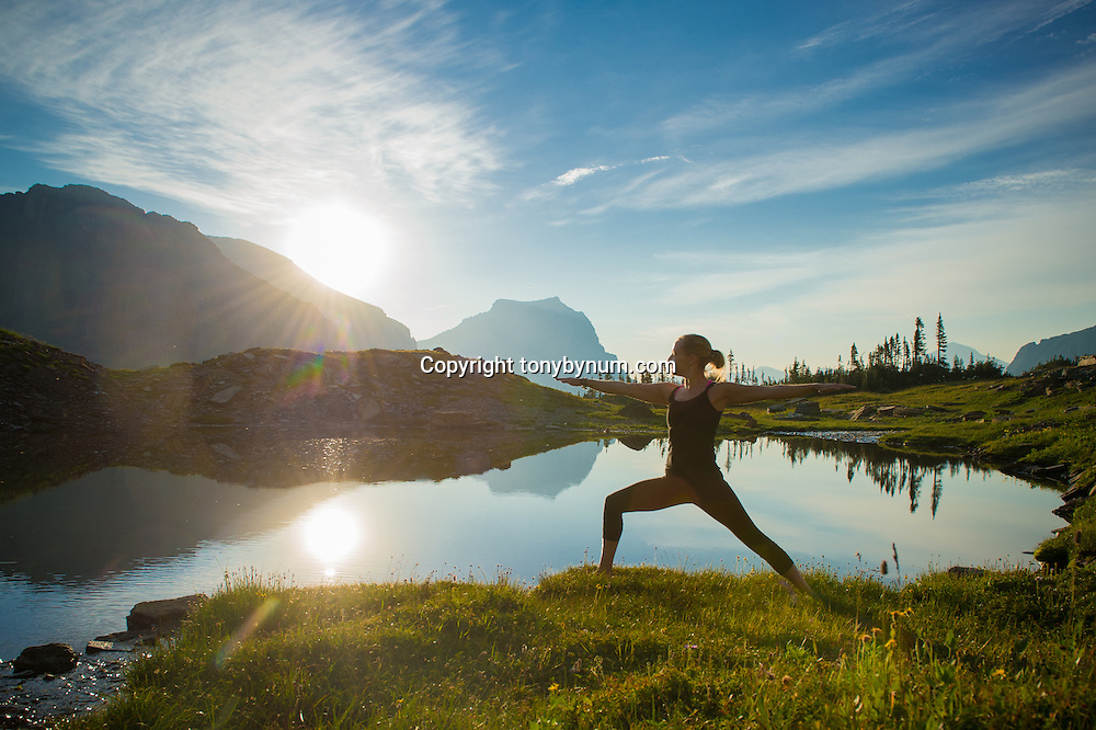dramatic morning sun rise on lake with woman doing yoga in mountains