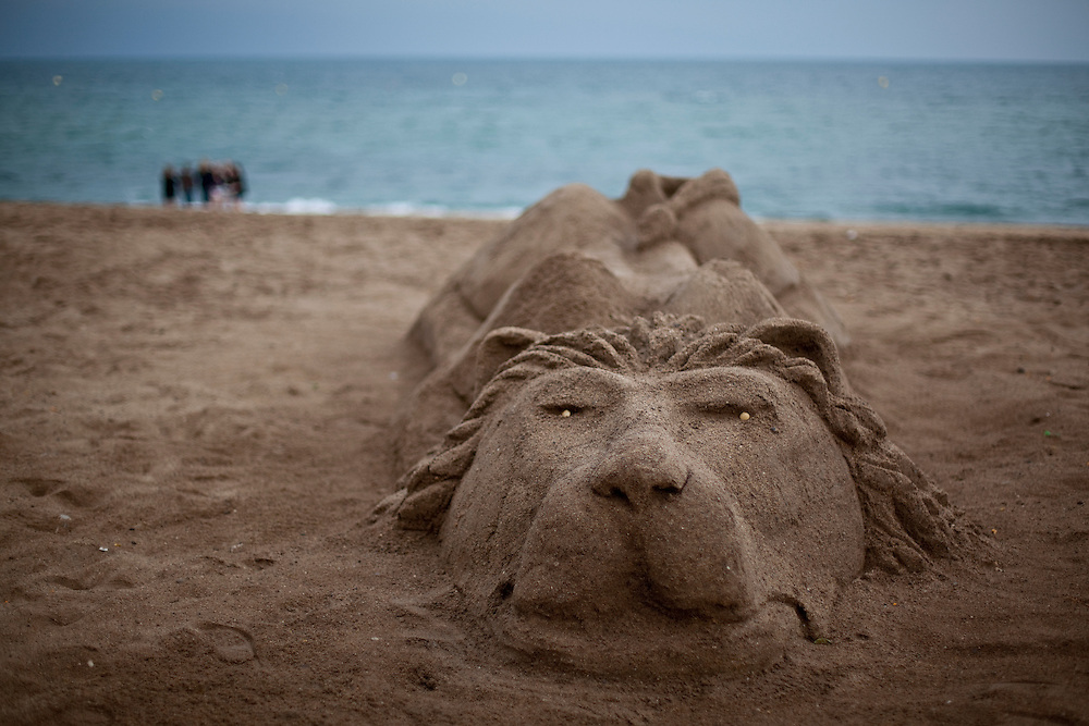Lion figure made out of sand at sunset at one of the beaches of Barcelona. Catalonia. (Spain)