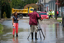 23 July 2013. New Orleans, Louisiana.<br /> Fox 8 local reporter Leigh Isaacson stands in flood water following a major break in an old 30-inch water main, officials and workers from New orleans Sewerage and Water board struggle to contain the millions of gallons of water flooding homes and streets in The Carrolton neighbourhood. Huge investment in public infrastructure is required to repair and upgrade the ageing water delivery system in the city. Following the break, low water pressure and a public boil advisory affected tens of thousands of Uptown residents.<br /> Photo; Charlie Varley