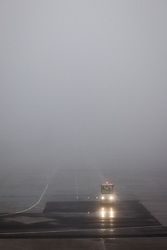 © Licensed to London News Pictures . 09/01/2013 . Manchester , UK . Airport maintenance vehicle on the runway in thick fog . Thick fog is causing flight delays and cancellations in the North of England today (9th January 2013) . Photo credit : Joel Goodman/LNP