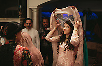 "Mavara Agha adjusts her veil shortly after being married at her childhood home in Oak Brook. Agha said that community ""in a religious and a cultural context is a huge part of a wedding…There are a lot of Pakistani Muslims in Oak Brook, and they all live pretty close to each other. Growing up we had a lot of get-togethers in my home, so having such a significant moment in my home and in front of my community meant a lot to me."" 