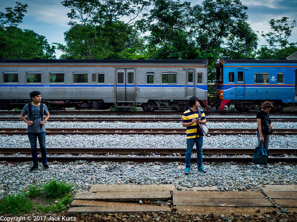 31 MAY 2017 - CHACHOENGSAO, THAILAND:  Passengers wait for a Bangkok bound train at the train station in Chachoengsao, a provincial town about 50 miles and about an hour by train from Bangkok. The train from Chachoengsao to Bangkok takes a little over an hour but traffic on the roads is so bad that the same drive can take two to three hours. Thousands of Thais live outside of Bangkok and commute into the city for work on trains, busses and boats.      PHOTO BY JACK KURTZ