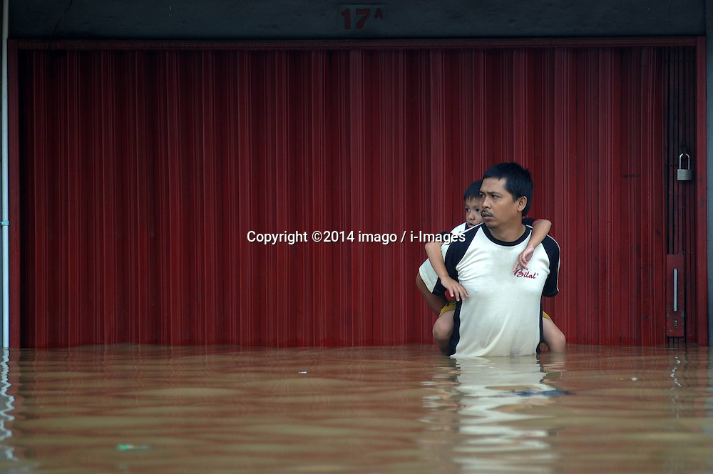 60915389<br /> A man carries his child in floodwater in Jakarta, Indonesia, Jan. 13, 2014. Indonesia s capital Jakarta is taking precautions to ensure the safety of people from possible bigger floods as more than 5,000 people have been displaced by the waters so far, official said here on Monday, 13th January 2014. Picture by imago / i-Images<br /> UK ONLY