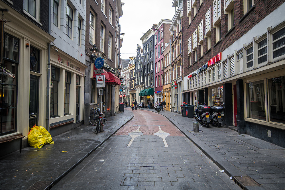 View down a narrow street with various restaurants and hotels, Amsterdam, Netherlands