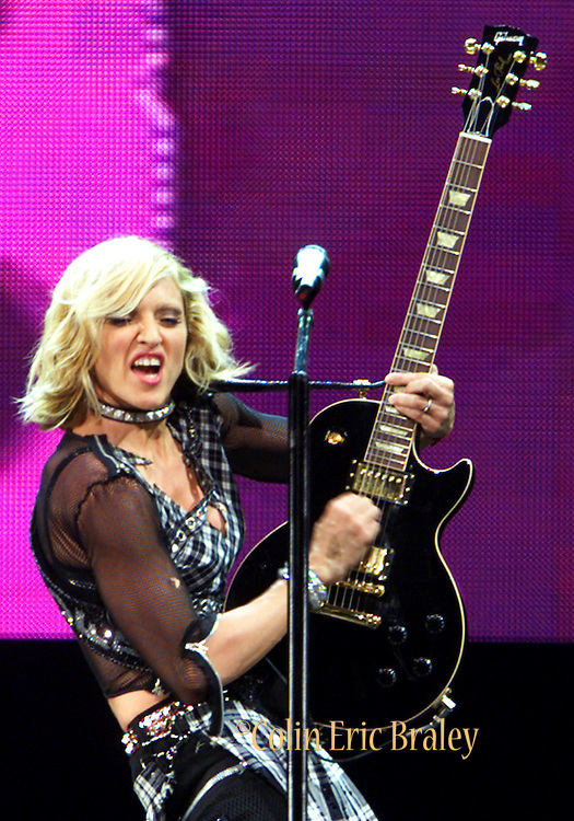 """International recording artist Madonna jams on a guitar during a performance at the National Car Rental Center in Sunrise, Florida, August 14, 2001 The """"Material Girl"""" added an additional show of her Drowned World Tour in the Miami area to accomodate her fans. Both shows have been sold out for several months. Stock/Colin Braley"""