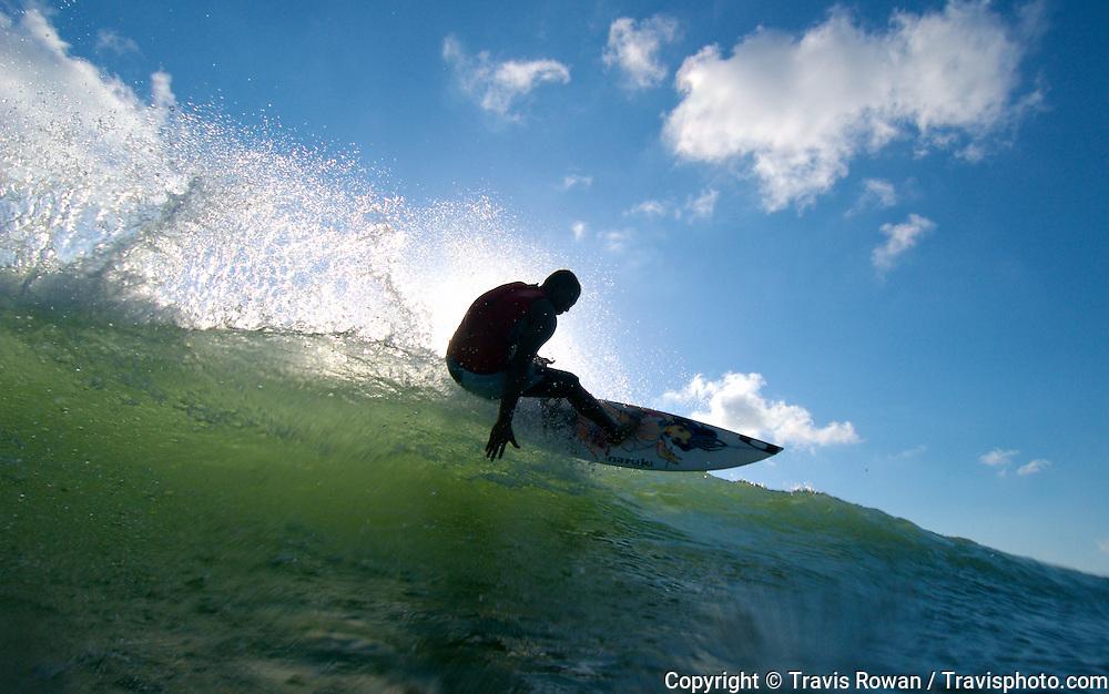Professional Balinese surfer, Mickey Sudena in action on Kuta beach, Bali.