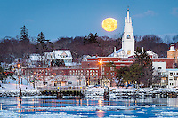 A full yellow moon sets behind the Winter Street Church in Bath, Maine. You can see Waterfront Park, shops on Front Street, and a house on the hill. The Kennebec River is full of ice, floating by in large pieces. Holiday lights still decorate the trees in the park. 