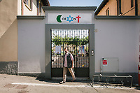 "COMO, ITALY - 21 JUNE 2017: Giusto Della Valle, a local priest who since 2011 has run a center on the outskirts of town where more than 50 migrants sleep at night, is seen here at the entrance of the San Martino di Rebbio parrish with the sign ""Coexist"", written a crescent moon, a star of David and Christian cross, in Como, Italy, on June 21st 2017.<br /> <br /> Residents of Como are worried that funds redirected to migrants deprived the town's handicapped of services and complained that any protest prompted accusations of racism.<br /> <br /> Throughout Italy, run-off mayoral elections on Sunday will be considered bellwethers for upcoming national elections and immigration has again emerged as a burning issue.<br /> <br /> Italy has registered more than 70,000 migrants this year, 27 percent more than it did by this time in 2016, when a record 181,000 migrants arrived. Waves of migrants continue to make the perilous, and often fatal, crossing to southern Italy from Africa, South Asia and the Middle East, seeing Italy as the gateway to Europe.<br /> <br /> While migrants spoke of their appreciation of Italy's humanitarian efforts to save them from the Mediterranean Sea, they also expressed exhaustion with the country's intricate web of permits and papers and European rules that required them to stay in the country that first documented them."