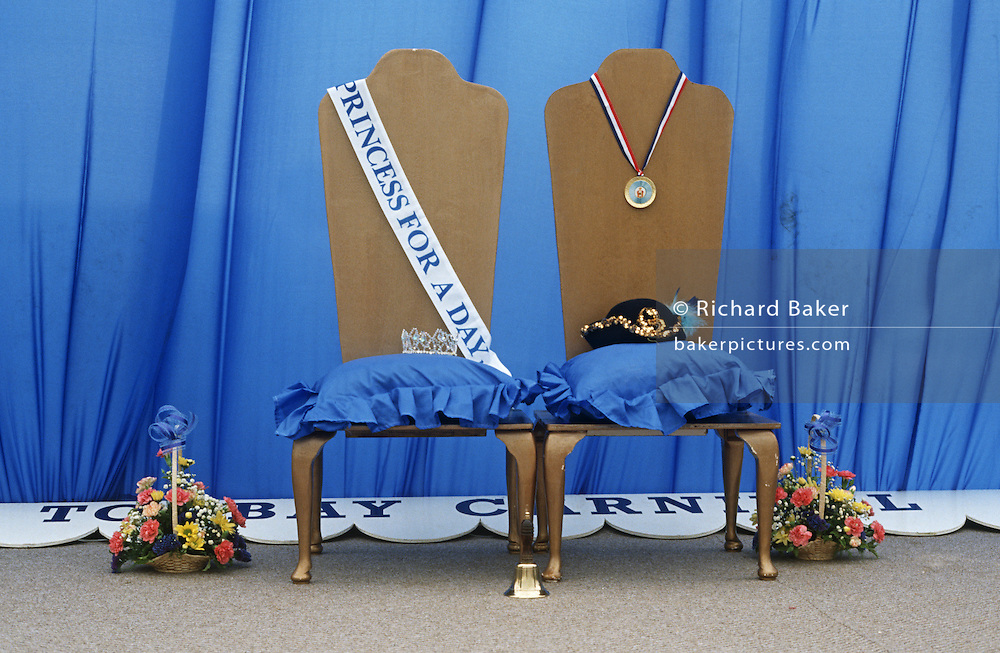Carnival Princess and Queen competition chairs, crown, sash and hat awaiting winning young ladies during Torbay seaside fair.