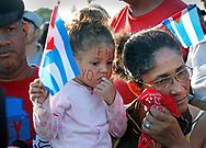 "A young child wears ""Yo Soy Fidel"" painted on her face as Cubans react to seeing the funeral procession carrying the ashes of Fidel Castro on the road to Cemeterio Santa Ifigenia in Santiago de Cuba on Sunday, December 4, 2016."