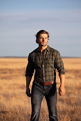 sexy man at sunset walking through a field