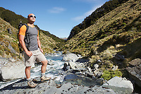 Hiker standing by edge of river