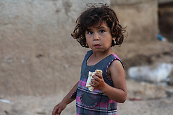 June 14, 2018 - Azaz, Syria - A kid walking with a snack in her hands..Eid al-Fitr atmosphere in Al-Tadhamon camp in the countryside of Azaz city where people live displaced from Aleppo city and the countryside. (Credit Image: © Muhmmad Al-Najjar/SOPA Images via ZUMA Wire)