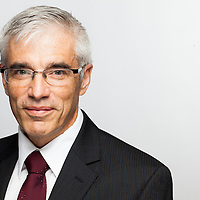 Professional headshot of man wearing glasses