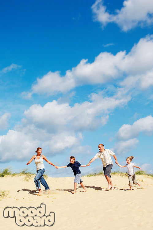 Family holding hands and running down sand dune on beach