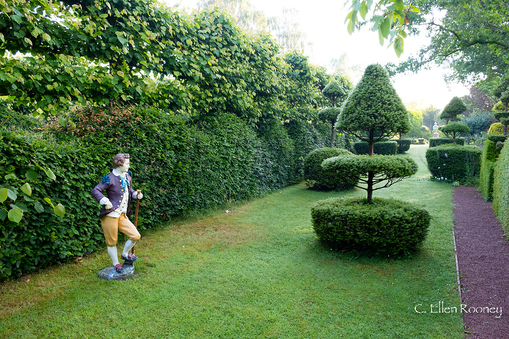 Taxus Baccata, Yew topiary in the Elizabeth Tudor Walk and a statue of a gentleman in period dress at the Laskett Gardens, Much Birch, Herefordshire, UK