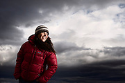 Dramatic moody sky portrait of Monique with Patagonia Fitz Roy down jacket.