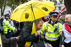 Whitehall, London, November 5th 2015. Pro Sisi demonstrators and counter protesters from UK Egyptian and human rights groups shout each other down outside Downing Street ahead of Egypt's President Abdel Fatah al-Sisi visiting Prime Minister David Cameron at No. 10. PICTURED: A pro-Morsi supporter is escorted by police past jeering Sisi supporters.