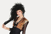 Portrait of young Goth woman with teased hair over gray background