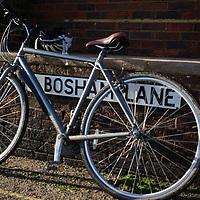 Bike parked beside road sign for Bosham Lane in Bosham  West Sussex, England