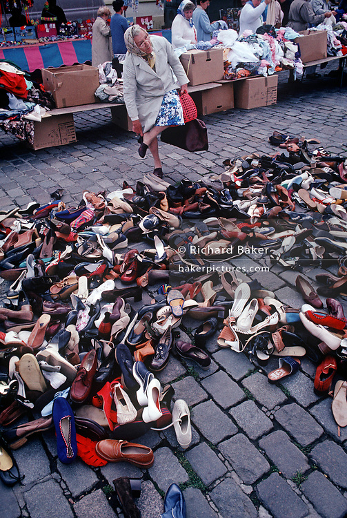 An elderly 1990s lady tries on a left show while standing over a choice of dozens of single items of footwear, in a daily market, on 11th May 1990, in Calais, France. (Photo by Richard Baker / In Pictures via Getty Images)