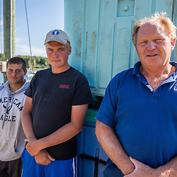 Hale Miller (right), owner of Miller's Wharf, with his son Eli (center), and Garrett Young. Eli (age 15) and Garrett (age 16) both fish 100 lobster traps with a student license. Tenants Harbor, Maine.