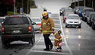 Two and a half year-old Imogen arrives hand in hand with her dad John Boyd at a Fireman's protest over contract negotiations at the opening of a new Fire Station in Mt Roskill, Auckland, New Zealand. September 2009. <br /> Photograph Richard Robinson.<br /> 2009 &copy; New Zealand Herald A Division of APN New Zealand Ltd.<br /> No Reproduction without prior written permission. Contact www.newspix.co.nz to licence photograph.