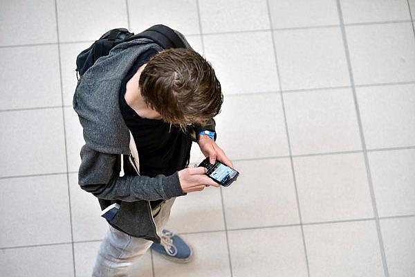 Nederland, Nijmegen, 27-8-2014 Jongeman, jongen, student, in een school bezig met social media op de gsm, smartphone,mobiel,mobiele, telefoon. Foto: Flip Franssen/Hollandse Hoogte