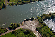Nederland, Overijssel, Gemeente Olst, 03-10-2010; stuw Olst, restant van de IJssellinie (waterlinie) gebouwd tijdens de Koude Oorlog. Lokatie van de stuw in rivier de IJssel, de betonnen weg vormde de ondergrond van de afsluitbare pijlerdam die uitkwam op het landhoofd (de betonnen muur). Oorspronkelijk stond op beide oevers zo'n landhoofd waartegen, aan de rivierzijde caissons afgezonken konden worden. Hierdoor zou het rivierwater het omliggende land doen overstromen (innunderen). Ook de haven voor de caissons, stroomopwaarts (rechtsonder), is nog aanwezig..Barrage Olst, remnant of the IJssel line (water line) was built during the Cold War. Location of the Barrage in the river IJssel, under the concrete road was the pillar dam, at the end of the road the and abutment (the concrete wall). Originally, such abutments were on both banks and were used to position caissons (on the river side) that subsequently could be sunk. This would make the river flood the surrounding land (inundation). The port for the caissons, upstream (right) is still present...luchtfoto (toeslag), aerial photo (additional fee required).foto/photo Siebe Swart