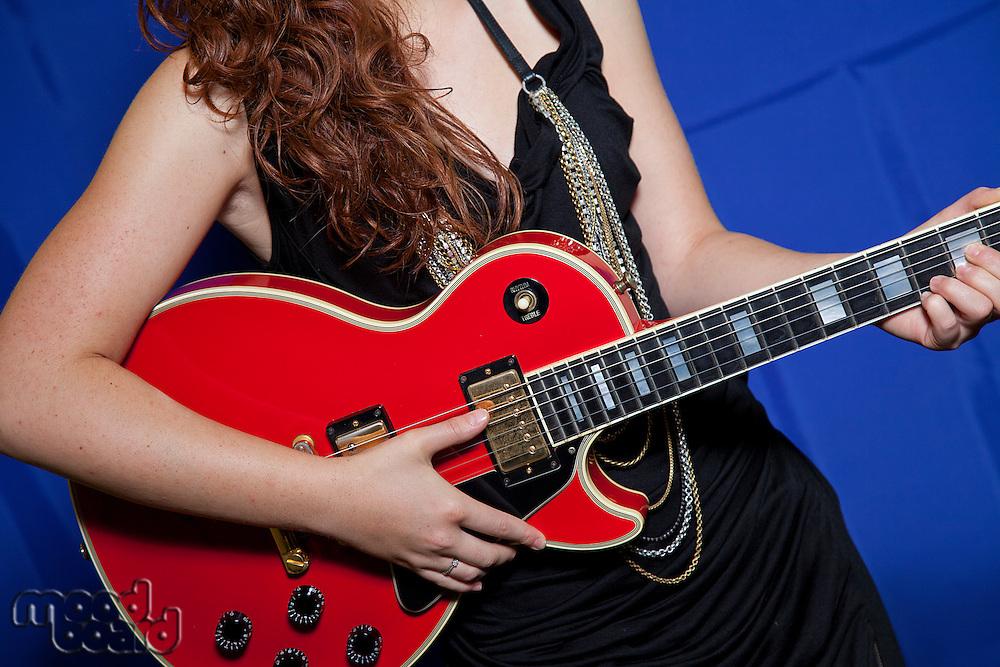 Midsection of teenage girl playing guitar
