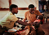 A mother and father share the daily chore of bathing their adopted son in the therapeutic feeding tent at the Mtendeli refugee camp near Kibondo, Tanzania.The couple assumed responsibilty for the malnourished child when his mother died recently.