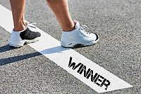 Man standing on stepping on white line with winner sign