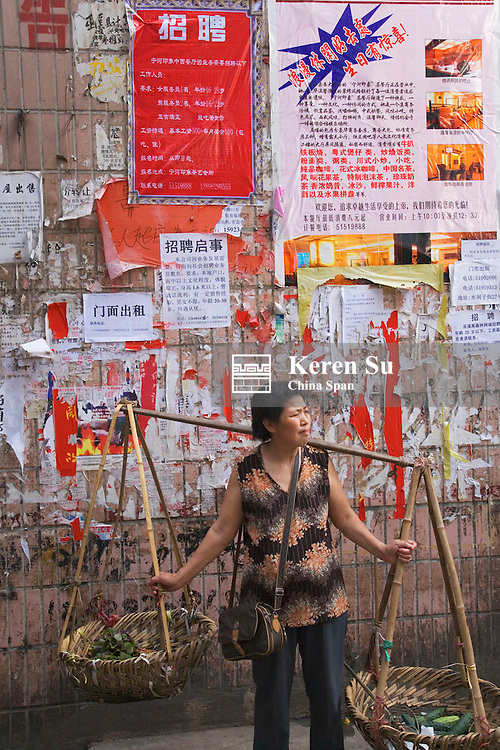 Woman carrying shoulder pole by wall with posters, Wuxi, Sichuan, China