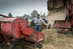 A farmhand works on a vintage baling machine at the Essex Country Show, Barleylands, Essex.