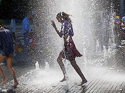 Image ©Licensed to i-Images Picture Agency. 03/07/2014. London, United Kingdom. Tourist children play with water coming out of ground-level fountains in one of the warmest days of the year with 28ºC in the shade. More London Riverside, City Hall area. Picture by Daniel Leal-Olivas / i-Images