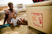 A mother sits with her child as they wait for a health worker to vaccinate the boy during a national polio immunization exercise in Salaga, northern Ghana on Thursday March 26, 2009.