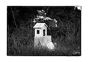 SHOT 11/21/11 1:41:09 PM - A tiny roadside capilla and cross along Carretera Federal 307 near Paamul, Mexico. Roadside capillas, or tiny chapels, in the Mexican state of Quintana Roo. The capillas are common along the roads and highways of Mexico which is heavily Catholic and are often dedicated to certain patron saints or to the memory of a loved one that has passed away. Often times they contain prayer candles, pictures, personal artifacts or notes. (Photo by Marc Piscotty / © 2011)