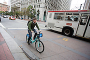 Een man rijdt op een fiets van Bay Area Bike Share, het deelfietssyteem in San Francisco. Het openbaar huursysteem is vanaf 2013 operatief in San Francisco en bestaat momenteel uit ongeveer 700 fietsen verdeeld over 70 geautomatiseerde stations. De fietsen kunnen bij elk station worden gepakt en op een willekeurig ander station worden neergezet. Per rit is het eerste half uur gratis, de huurfietsen zijn bedoeld voor korte ritten.<br /> <br /> A man rides a bike of the Bay Area Bike Share, the bike sharing system in San Francisco. The public rental system has been operative since 2013 in San Francisco and currently consists of about 700 bikes spread over 70 automated stations. The bikes can be picked up at each station and put down at any other station. Per trip, the first half hour is for free. The rental bicycles are provided for short journeys.