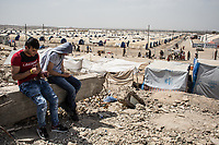 West Mosul residents wait for a bus for a refugee camp near Mosul, Iraq.