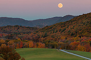 The nearly full moon rises over the Hudson Highlands and Schunnemunk Mountain, in the foreground at right, as seen from Salisbury Mills, New York.
