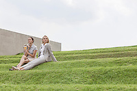 Full length of female business executives sitting on grass steps against sky