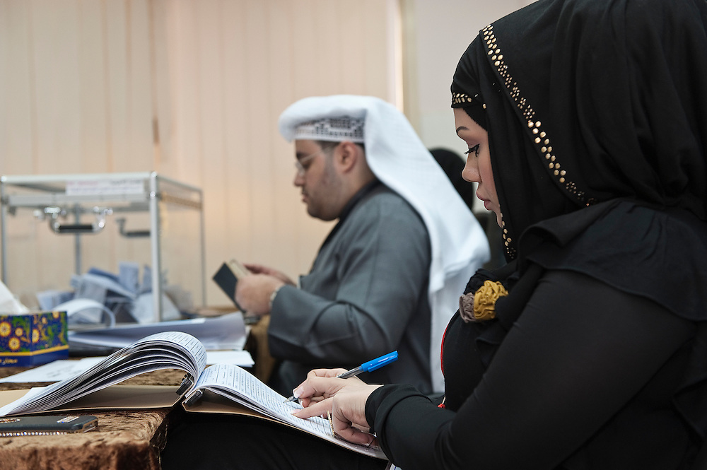 Elections officials checking the nationality card of a Kuwaiti woman voter against the roster of registered voters at a polling station in Kuwait City during the February 2 parliamentary elections. More than 400,000 Kuwaiti men and women are eligible to vote to choose from among some 285 candidates for a new 50-seat National Assembly (parliament).