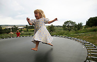 Havilah Jeub, 3, plays on the family trampoline outside their home in Monument, Colorado July 19, 2009. Quiverfull believers Wendy and Chris Jeub have 15 children and would be happy to have more if God wills it they say. Picture taken on July 19, 2009. REUTERS/Rick Wilking (UNITED STATES SOCIETY RELIGION)